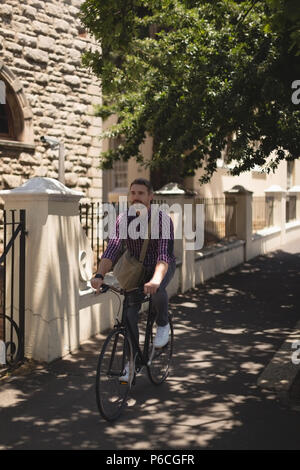 Man riding bicycle on street Banque D'Images