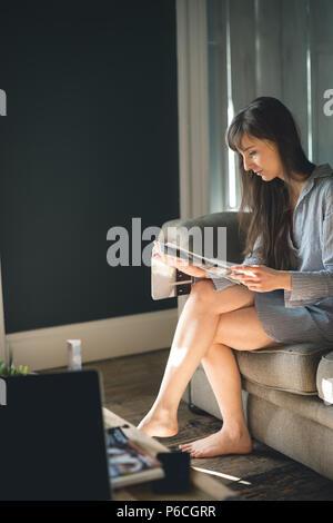 Woman Reading magazine dans la salle de séjour