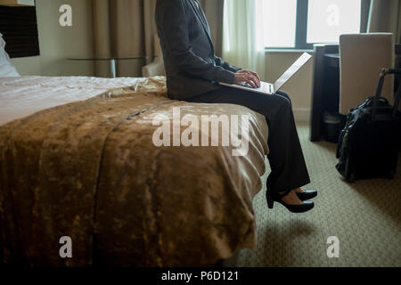 Businesswoman using laptop on bed Banque D'Images