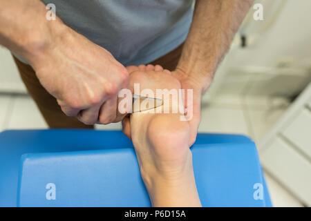 Physiothérapeute massage des jambes donnant à la femme Banque D'Images