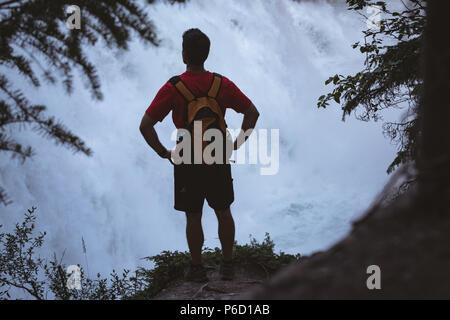 Homme debout avec les mains sur la hanche près de waterfall Banque D'Images