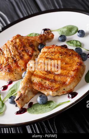 Délicieux steak de porc grillé, sauce aux bleuets avec de délicats et épinards libre sur une plaque sur une table verticale. Banque D'Images