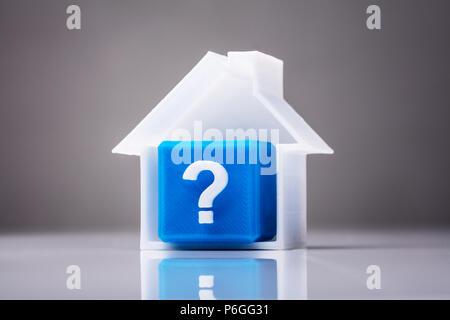 Cube bleu avec un point d'interrogation Signer dans maison modèle sur fond réfléchissant Banque D'Images