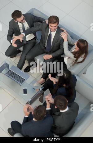 Joyeux jeunes gens d'affaires, offrant un rapport de cinq ans tandis que leurs coll Banque D'Images