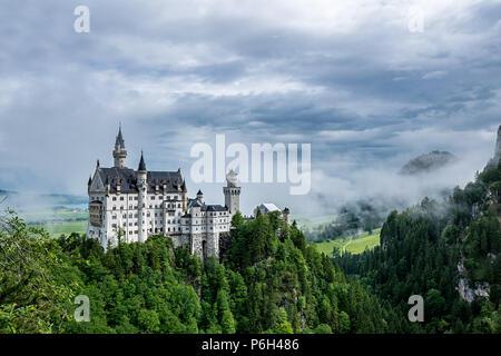 Château de Neuschwanstein en Bavière appelé avec des nuages dans le ciel et un peu de brouillard sur une journée ensoleillée Banque D'Images