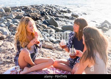 Groupe de jeunes femmes ami boire ensemble un jus de fruit sur un rock beach à Ténérife. Relation pour une équipe à l'ejoy locations et de bonheur. Banque D'Images