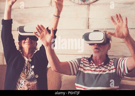 Couple de senior adult caucasian profiter avec la technologie casque goggled et jouer dans realuty virtuel ensemble s'amusant à essayer de nouvelles expériences. Banque D'Images