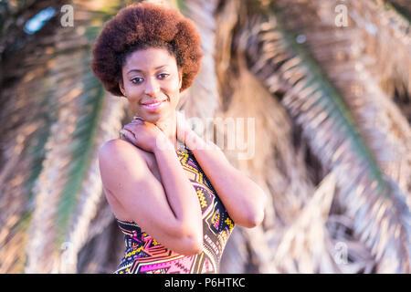 Cute smiling afro africaine fille modèle poser dans un endroit tropical. l'heure d'été et l'activité de loisirs pour la belle jeune femme souriant sous le soleil avec