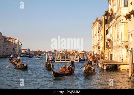 Les touristes profiter des promenades en gondole romantique au coucher du soleil sur le Grand Canal, Venice, Veneto, Italie. Heure d'Or avec reflets. Banque D'Images