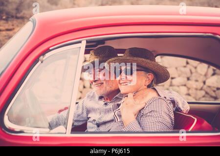 Couple de personnes âgées avec chapeau, avec des lunettes, avec des cheveux gris et blanc, avec chemise décontractée, sur vintage voiture rouge en vacances profiter du temps et de la vie. Avec un chee Banque D'Images