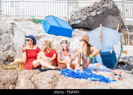 Groupe de femelles amis assis sur les rochers près de la mer et profiter des activités de plein air et de loisirs de vacances de détente dans l'amitié. Heureux peo vie Banque D'Images