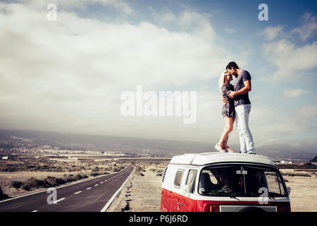 Beau couple dans l'amour debout sur le toit d'un van legendaru vintage. transport et notion de famille. longue route asphaltée en arrière plan et du ciel Banque D'Images