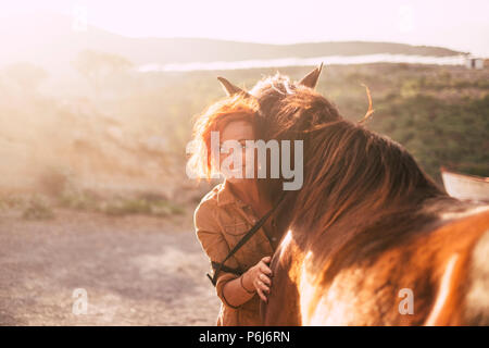 Cheveux rouge belle dame alternative hug ses meilleurs amis animal cheval au coucher du soleil dans la campagne. rétro-éclairage en arrière-plan et de l'amour, concept Banque D'Images