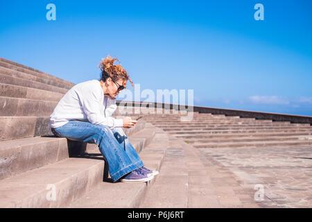 Seul moyen-âge femme à travailler avec un smartphone assis sur une longue belle Joly en milieu urbain concours. les loisirs avec tehnology concept pour dame moderne Banque D'Images