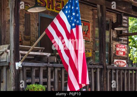 Drapeau américain sur le porche d'une boutique d'antiquités dans les contreforts des Blue Ridge Mountains. (USA) Banque D'Images