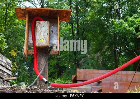 L'alimentation temporaire Tableau électrique monté sur un tableau avec un câble branché sur le site de construction Banque D'Images