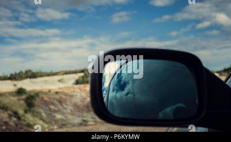 Réflexions du vieil homme dans le miroir dans la voiture close-up dans des mines Zaranda avec ciel bleu avec des nuages, Espagne