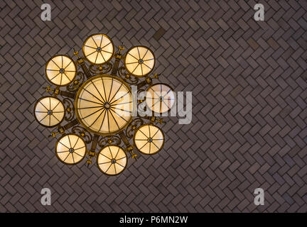 Belle lampe ornée de style herrinbone suspendue au bout d'un acrhed plafond dans la zone de réception sur Ellis Island, au large de Manhattan, New York City lampe ornée h Banque D'Images