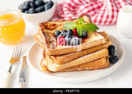 Pain doré aux bleuets frais, framboises et miel sur plaque blanche. Délicieux petit-déjeuner Banque D'Images