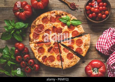 Pizza au pepperoni fait maison sur la vieille table en bois rustique. Vue d'en haut, l'image aux couleurs Banque D'Images