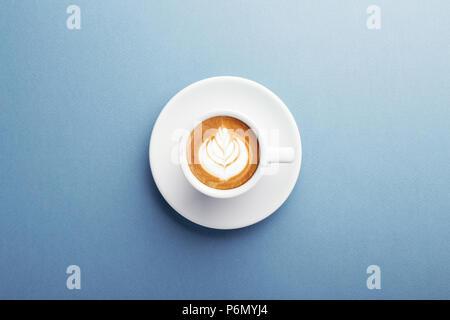 Une tasse de Cappuccino avec belle latte art sur fond bleu. Vue de dessus, le centre de la composition. Banque D'Images