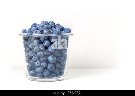 Les bleuets frais biologiques dans la cuvette en verre transparent isolé sur fond blanc. Savoureux sucré myrtilles en pot. Vitamines naturelles de la saison estivale et d'antioxydants. Saine alimentation et nutrition concept Banque D'Images