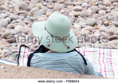 Lone woman sitting on beach portant un chapeau de soleil, Greenbottom, Devon, England, UK Banque D'Images