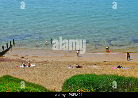 Enfants bravant la mer glaciale sous le soleil d'été à Milford on Sea, Hampshire