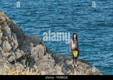 Un homme tatoué sur les rochers et debout tenant un filet de pêche et une bouteille. Banque D'Images