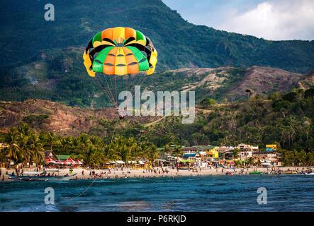 Le parachute ascensionnel sur la plage blanche remplie de centaines de personnes en vacances à Puerto Galera, Oriental Mindoro, Philippines. Banque D'Images
