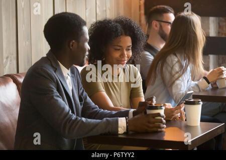 Les personnes bénéficiant de multiraciale d'aller pendant les pauses café in cafe Banque D'Images