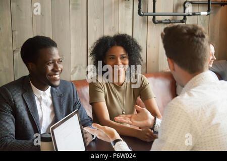 Consultant du Caucase de parler à des clients noirs in coffee shop Banque D'Images