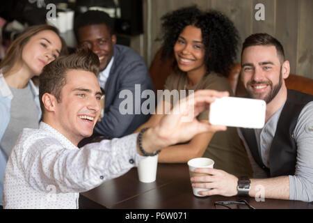 Divers collègues smiling pour photo de groupe reposant dans cafe