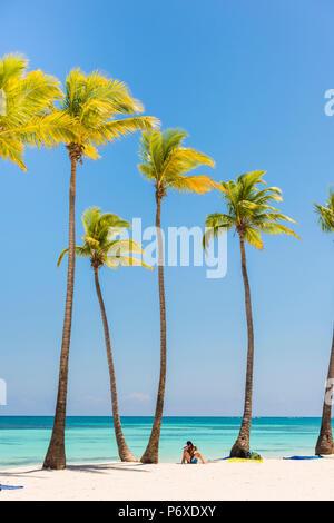Juanillo Beach (playa Juanillo), Punta Cana, République dominicaine. Couple sur une plage bordée de palmiers (MR). Banque D'Images