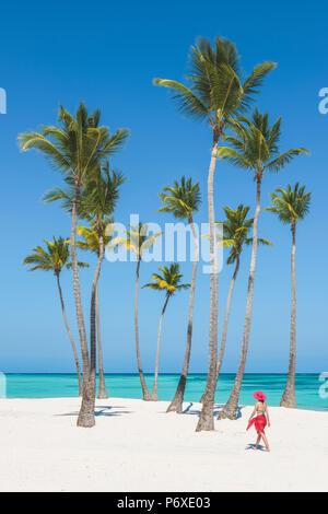 Juanillo Beach (playa Juanillo), Punta Cana, République dominicaine. Femme marche sur une plage bordée de palmiers (MR). Banque D'Images