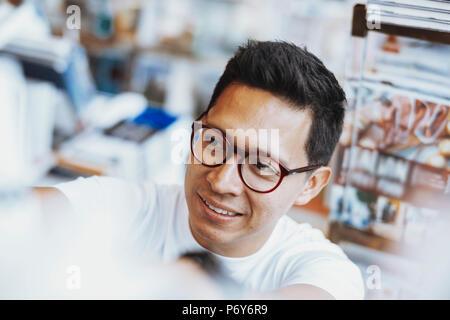 Jeune homme à lunettes atrractive livre choisir un livre sur l'étagère. Banque D'Images