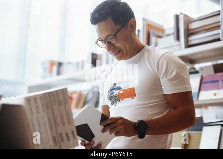 Jeune homme à lunettes lecture livre dans un magasin de livre. Banque D'Images
