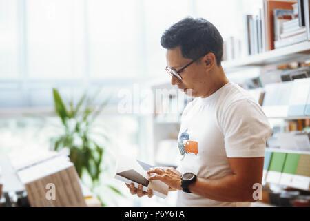 Les jeunes ours à lunettes man reading book in book store moderne et lumineux. Banque D'Images