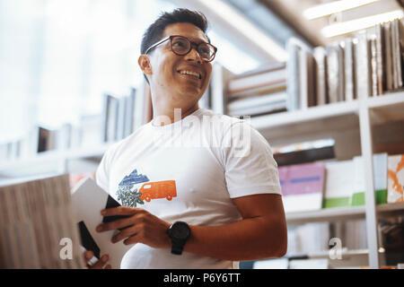 Jeune homme heureux et lecture à côté dans un magasin de livre lumineux et modernes. Banque D'Images