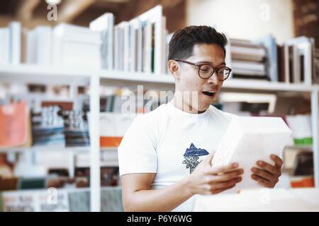 Jeune homme à lunettes attrayants holding book et démontrer surpris face. Banque D'Images