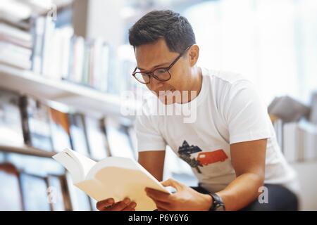 Jeune homme à lunettes assis dans un magasin de livre et de la lecture livre avec couvercle blanc Banque D'Images