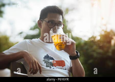 Jeune homme à lunettes buvant de la bière. Banque D'Images