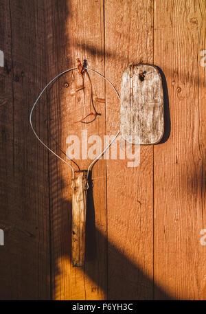 Vieux outils de pêche à la main accroché sur le mur en bois d'orange sur la lumière du soleil Banque D'Images