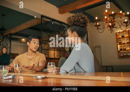 Amis assis dans un bar et prendre un verre ensemble couner Banque D'Images