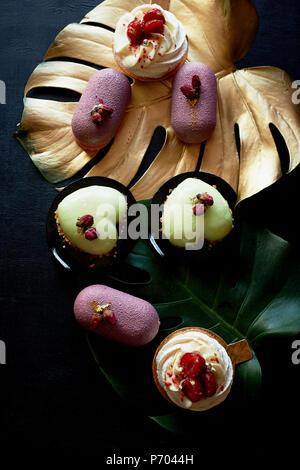 Gâteaux Moscovie violet et jaune citron. Pistache et fruits. Anna Pavlova meringuée . Art culinaire de la feuille d'or monstera Banque D'Images