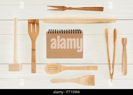 Vue de dessus du manuel et des ustensiles de cuisine en bois sur le tableau blanc Banque D'Images