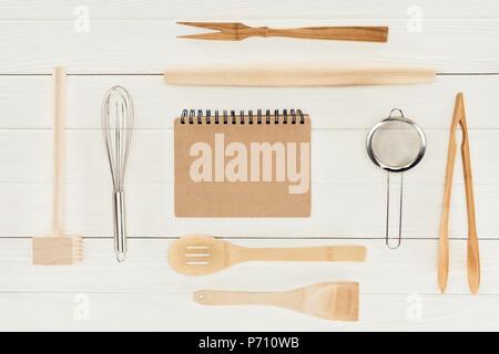 Vue de dessus du manuel et des ustensiles de cuisine en bois sur tableau blanc Banque D'Images