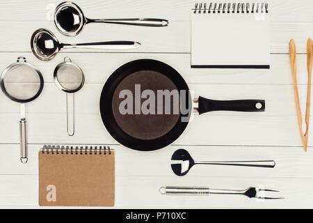 Vue de dessus de manuels scolaires, poêle et des ustensiles de cuisine sur la table en bois blanc Banque D'Images