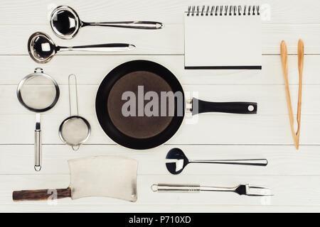 Vue de dessus du vide manuel, poêle, butcher ax et des ustensiles de cuisine sur la table en bois blanc Banque D'Images