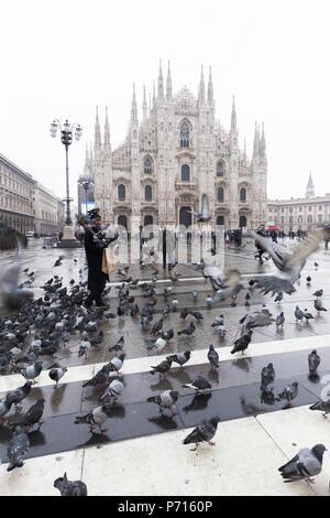 Une personne se nourrit les pigeons dans la Piazza Duomo (Place de la cathédrale), Milan, Lombardie, Italie du Nord, Italie, Europe Banque D'Images